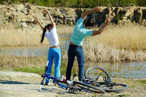 duas pessoas se alongando ao lado de um lago