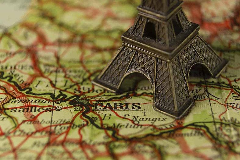 imagem de uma torre de parís de metal em cima de um mapa