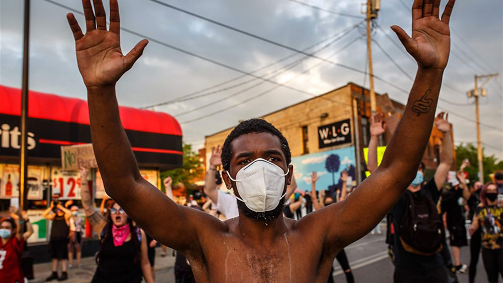 PHOTO: A black man at a protest. He wears a mask and holds both hands in the air. He is surrounded by other protestors.