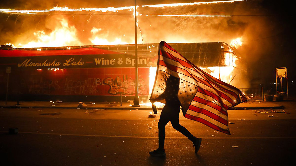 PHOTO: A protestor walks in front of a burning building. He carries an American flag upside down in protest.