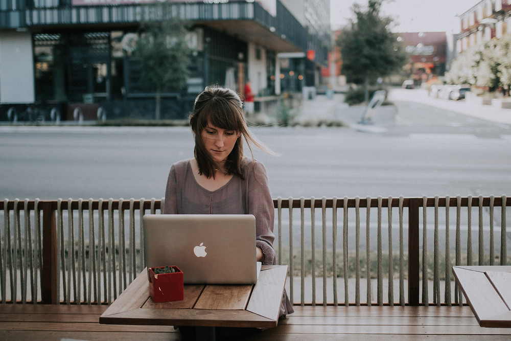 brunette woman with bangs looking down at computer while seated outside a cafe in an urban setting