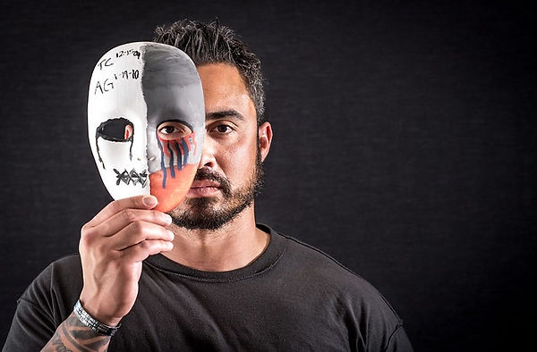 A man with a beard, dark hair, wearing a black t-shirt holding up a paper painted mask for TBI