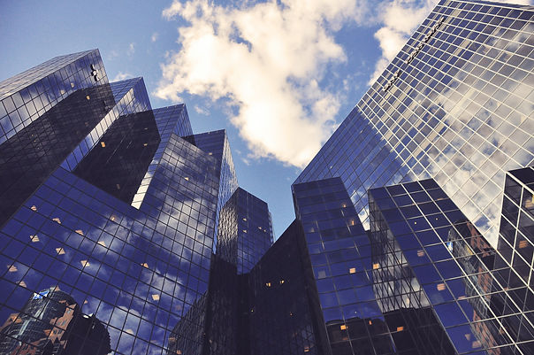 Borack Law Group offers services in Business & Commercial law. Multiple commercial buildings with glass windows rise towards a blue sky with fluffy white clouds