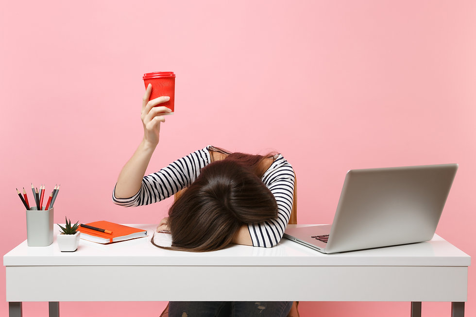 Exhausted woman laid her head down on the table holding cup of coffee or tea sit, work at