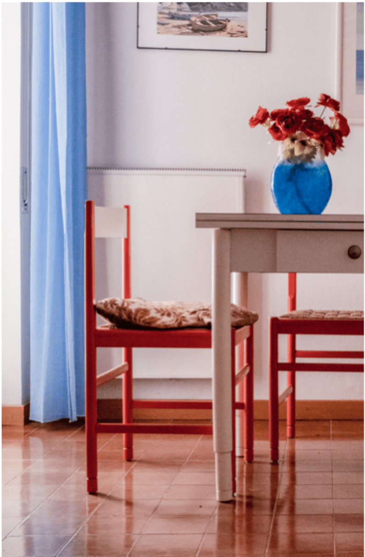 tavolo bianco con vaso e sedie arancioni