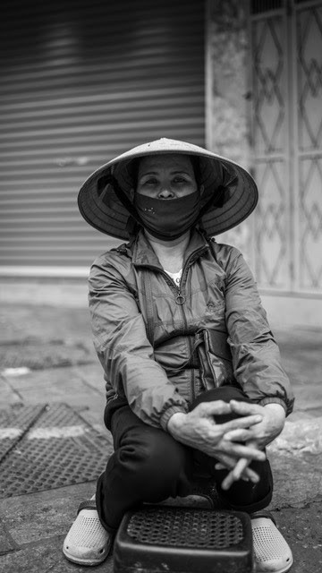 Life goes on in Hanoi as a masked Vietnamese woman awaits a customer.