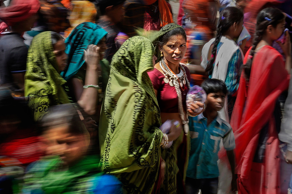 This pic was taken at a tribal festival, called Gher fair in a small village of Gujarat State in India. The place was quite crowded. Movement was quite uneven. I have used slow shutter technique with panning to capture this pic.