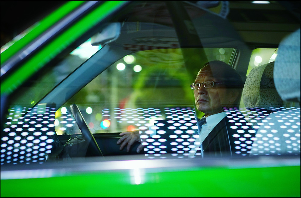 This was shot in Ikebukuro, Tokyo.  The photo shows a taxi driver waiting with white neon reflected in his window.
