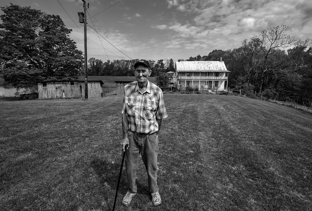 A Visit to the Old Homeplace - This image if of a man visiting the old home and farm where he grew up in rural West Virginia.  He and his brothers and sisters all own a part of the farm, where many of the historic buildings are well preserved.