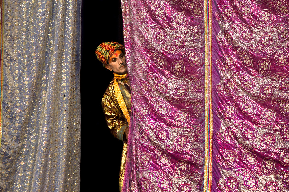 This pic was taken during Ram Leela a tradition drama performed during Navratri festival of India. I have captured a candid moment where a performer was pipping through the curtain when other artists were performing on the stage.