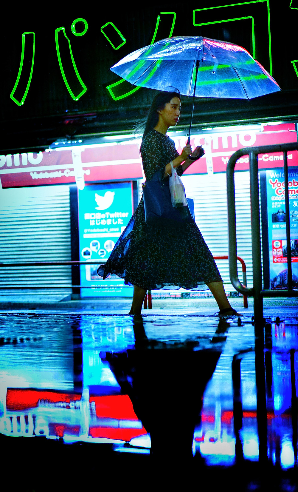 This photo was shot in Shinjuku, Tokyo during a typhoon.  In the photo a woman walks past some green neon holding an umbrella.