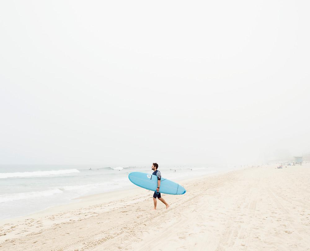 A surfer walking through the fog in Manhattan Beach, California.