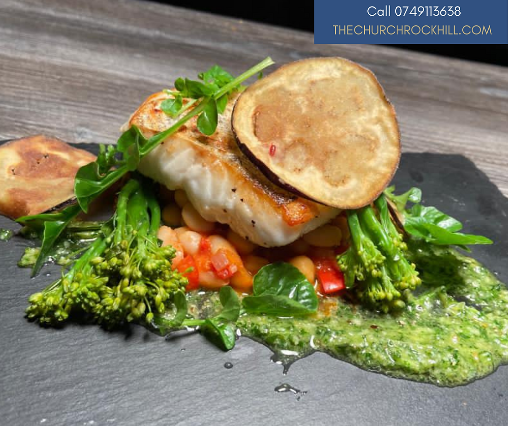 Pan Fried Hake with pine nut and wild garlic (or basil) pesto, cassoulet of pulses and an aubergine crisp for decoration presented on a black slate