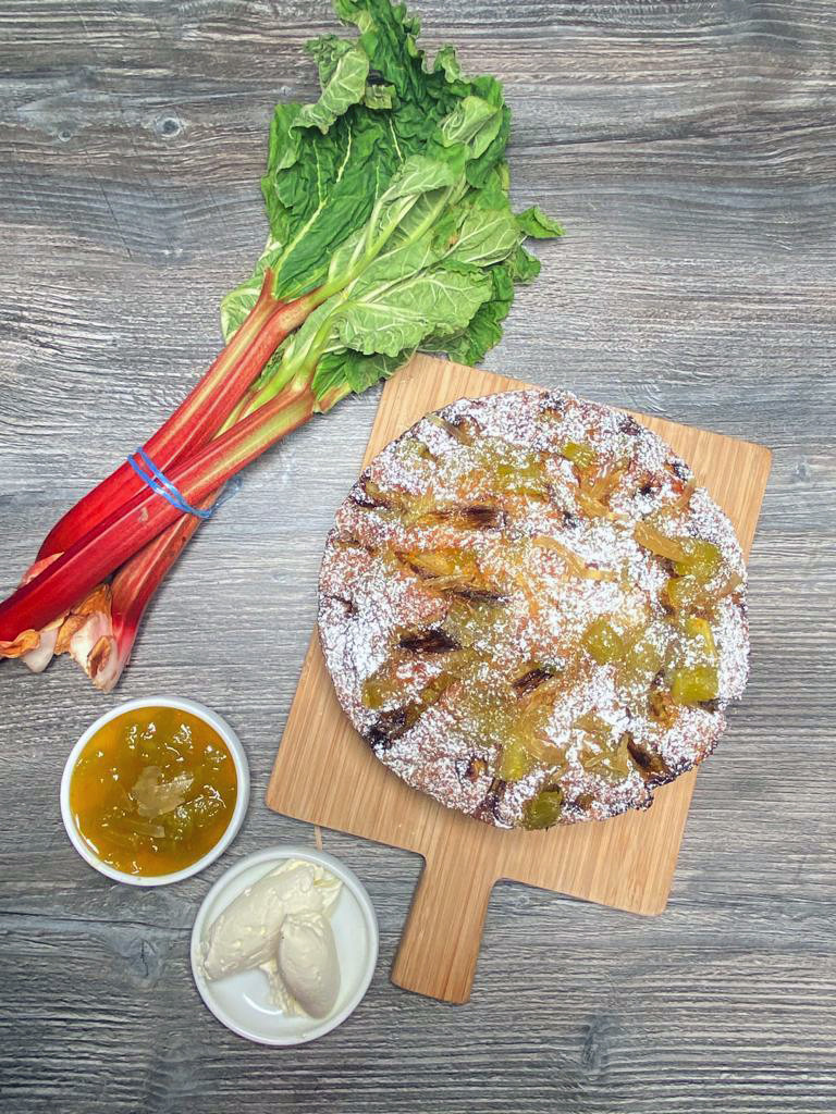 A large rhubarb cake sits on a wooden cutting board next to stalks of rhubarb tied with bright blue twine, a two small white dishes of rhubarb compote and homemade vanilla ice cream