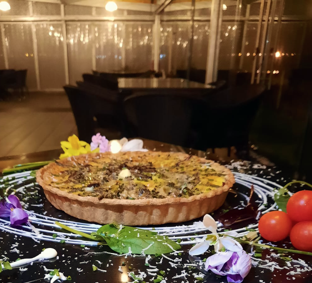 Side angle of first of the season asparagus, red onion and cheese tart at The Church, with Spring flowers and grated cheese for decoration.  In the background are the soft golden yellow lights on The Church glass walled terrace lit for nightime.