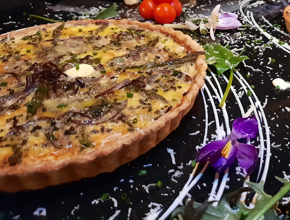 A 24cm first of the season asparagus, red onion and cheese tart at The Church, with Spring flowers and grated cheese for decoration.