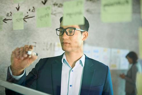 businessman-drawing-on-glass-wall-JUXF6S