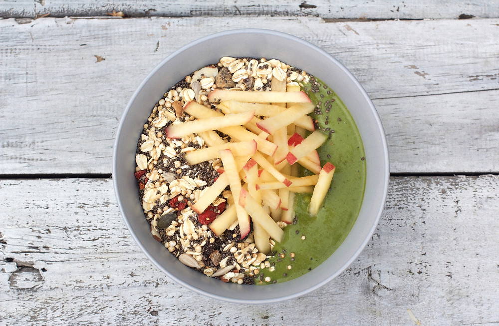green smoothie bowl with delicious homemade muesli and sliced apple
