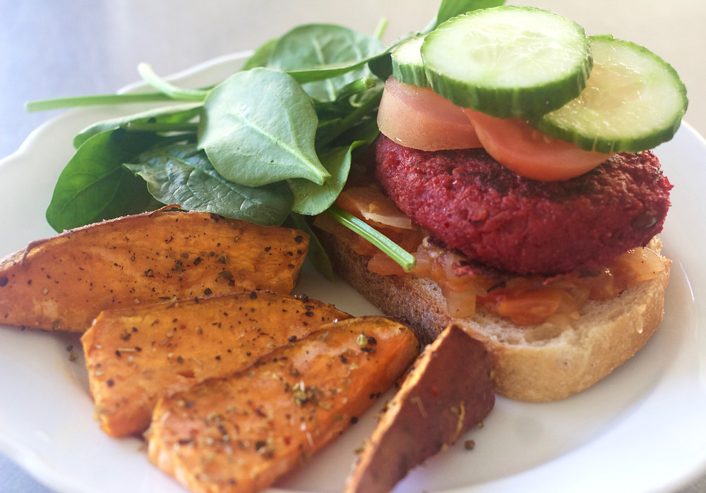 Lentil burger served with homemade tomato relish and sweet potato wedges