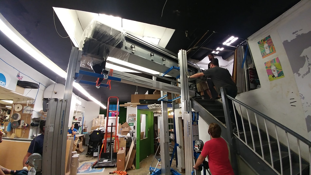 Riggers lowering the machine into our shop.