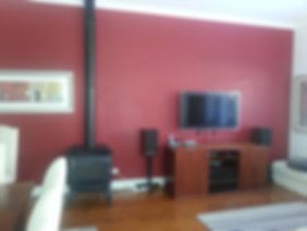 Living space prior to renovationwith red wall and combustion heater