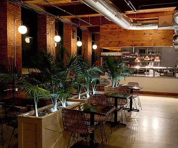 Palm fronds, rattan chairs, restaurant, open kitchen, exposed brick