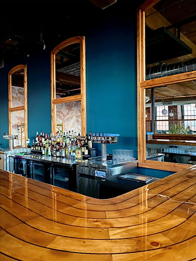 dark teal wall, honey colored wood, mirrors, bar, alcohol, taps, daught beer