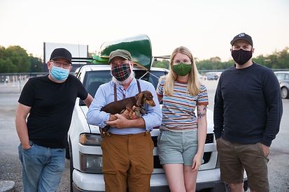 A group of masked people at a drive-in theater