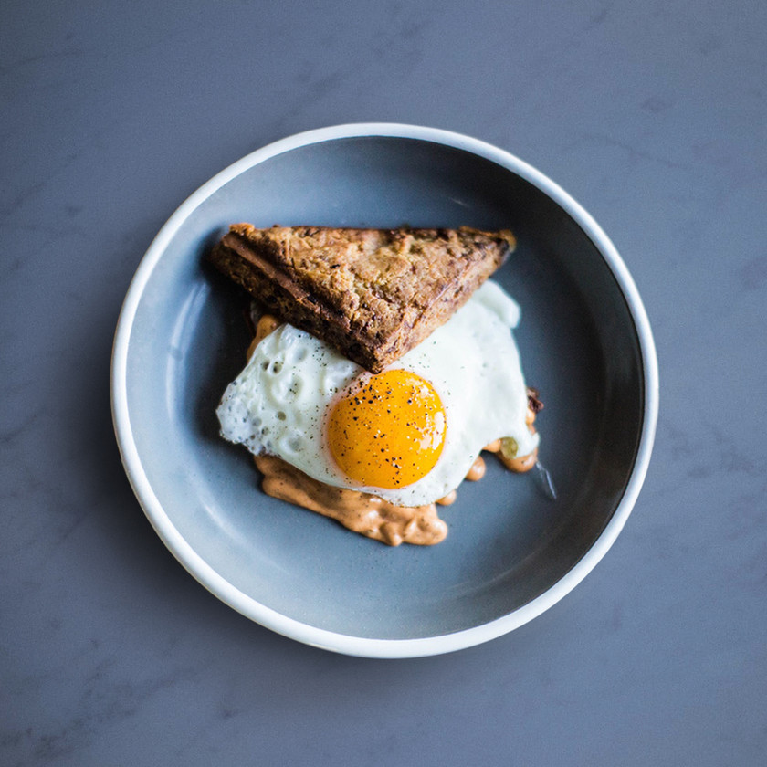 A sunnyside up egg between two pieces of toast served on a plate.