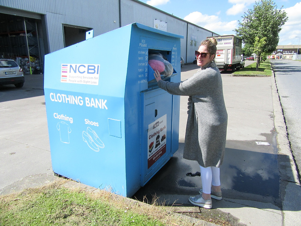 Image of woman smiling and donating a bag of clothes at one of NCBI clothing bank donations.