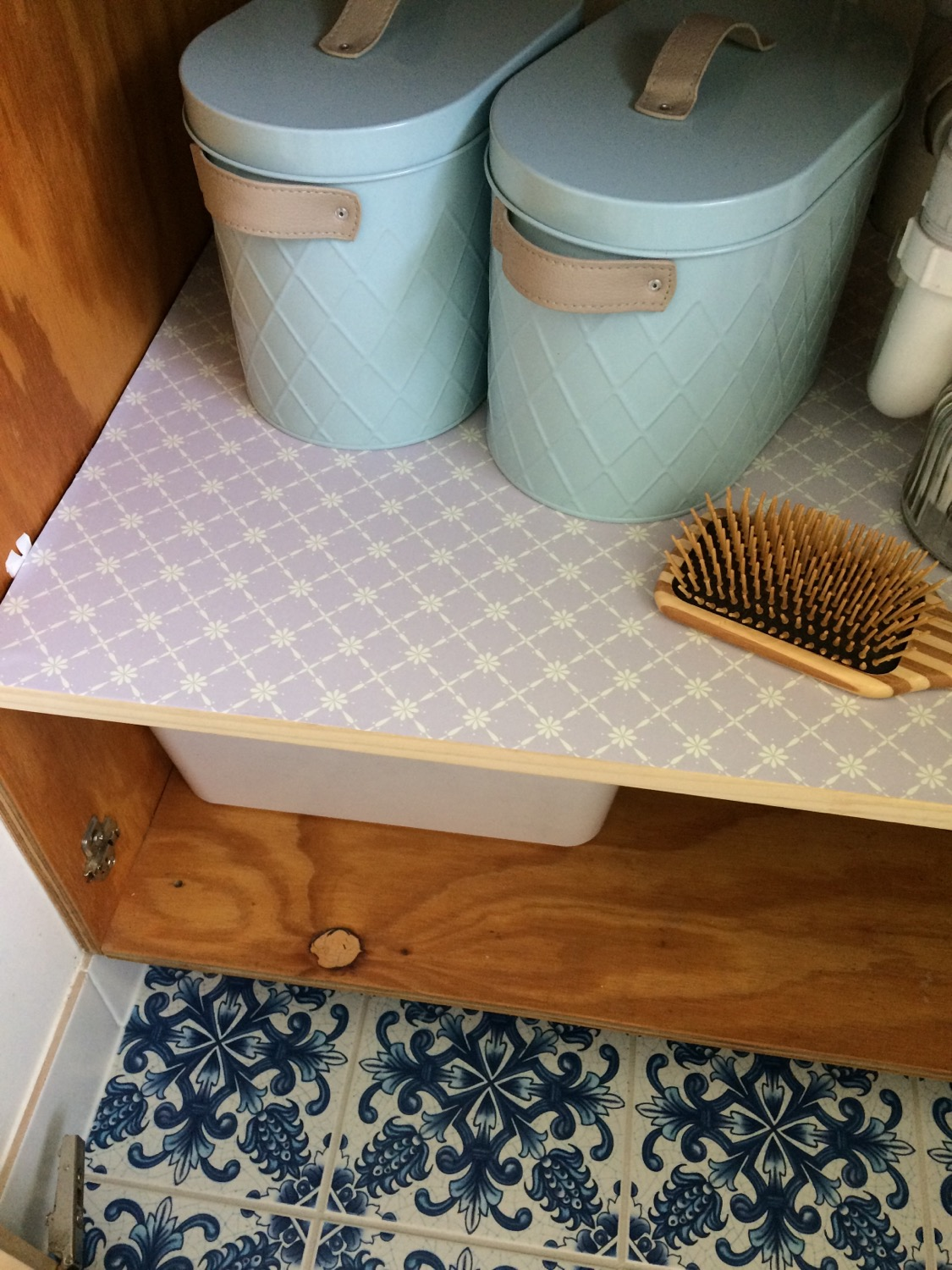 Woven wallpaper used to line bathroom shelves