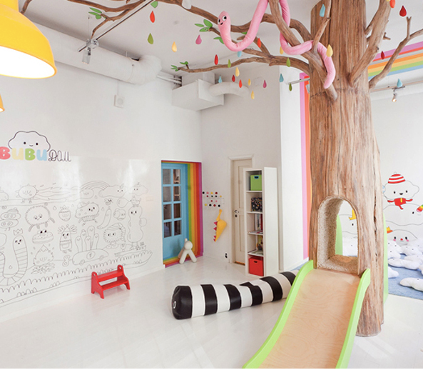 A hollow tree slide, cute wall decals, lots of bright colors