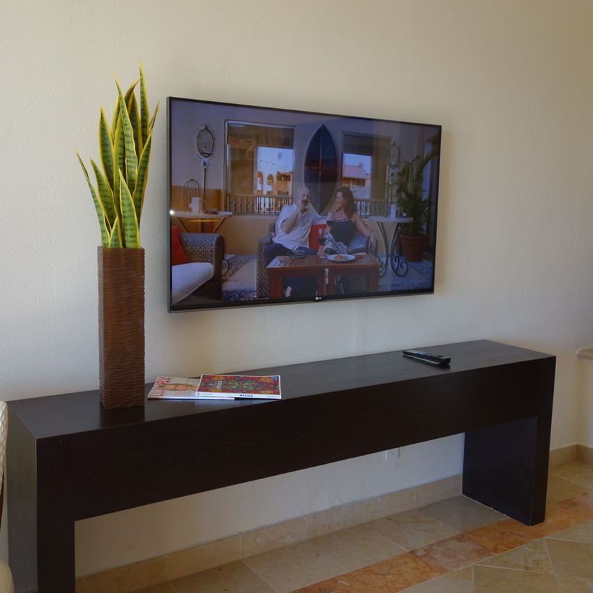 The TV is mounted to the wall and instead of a dresser, there is a console.