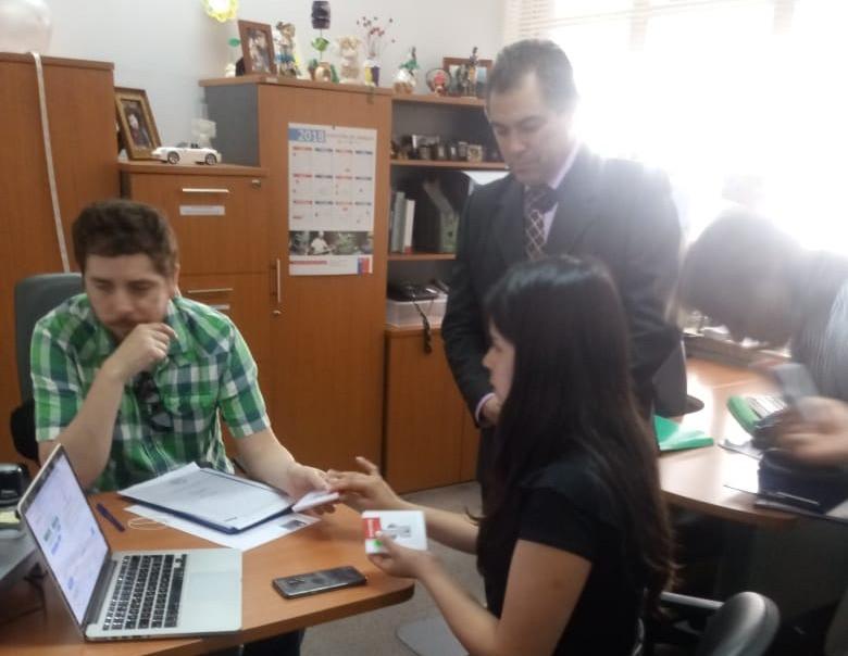 Representante de la empresa EVOTING junto al Ministro de Fe de la Inspección del Trabajo porceden a abrir la urna electrónica. El dirigente Marco Reyes, atento al proceso.