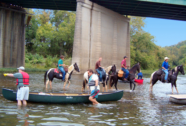 Horses & canoes in river