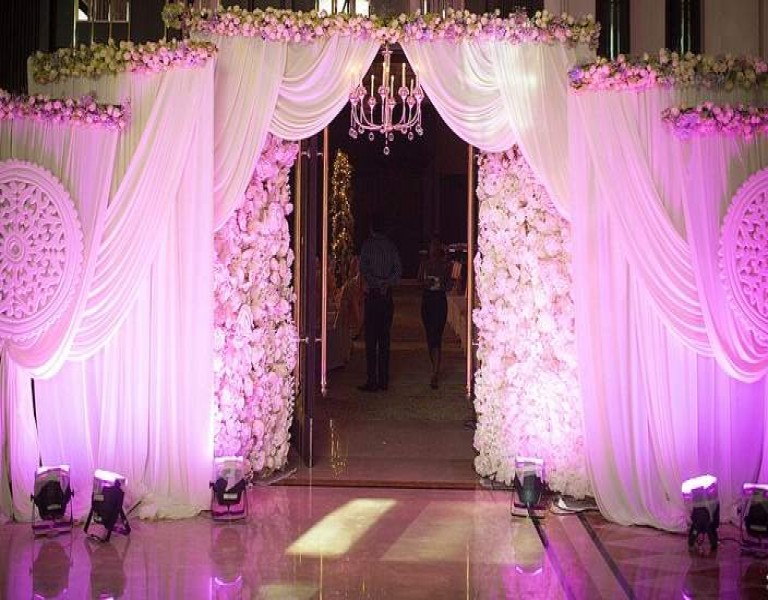 purple lights, grand entrance, white drapes, floral decor, layered drapes