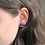 Bisexual pride stud earrings show the colors of the bisexual pride flag, pink, purple, and blue circle studs