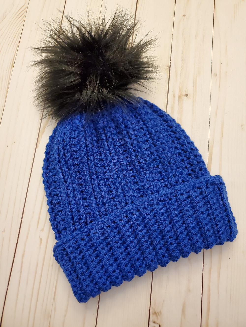 Blue crocheted beanie with a black faux fur pom on a white background