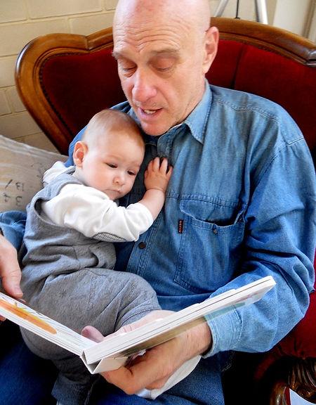 אמנון ז'קונט יושב עם ספר ותינוק