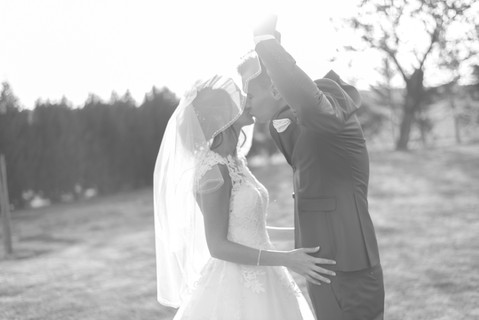 couple de mariés en noir et blanc. Le marié embrasse son épouse sous le voile