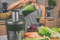 Woman juicing making green juice with ju