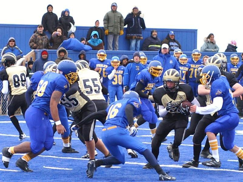 Barrow Whalers defenders try and tackle an opponent in Barrow, Alaska playing on new turf at Cathy Parker Field.