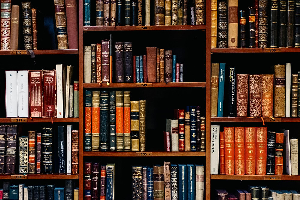 Antique library books on wooden shelves.