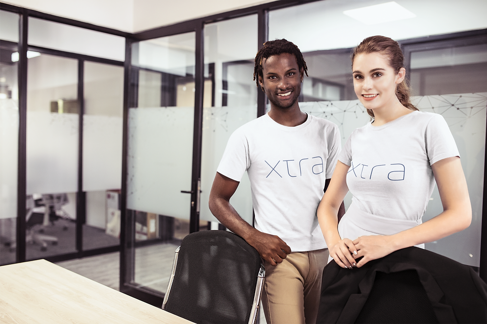 Black man and white girl wearing Xtra, Inc. t-shirts in an office meeting room.