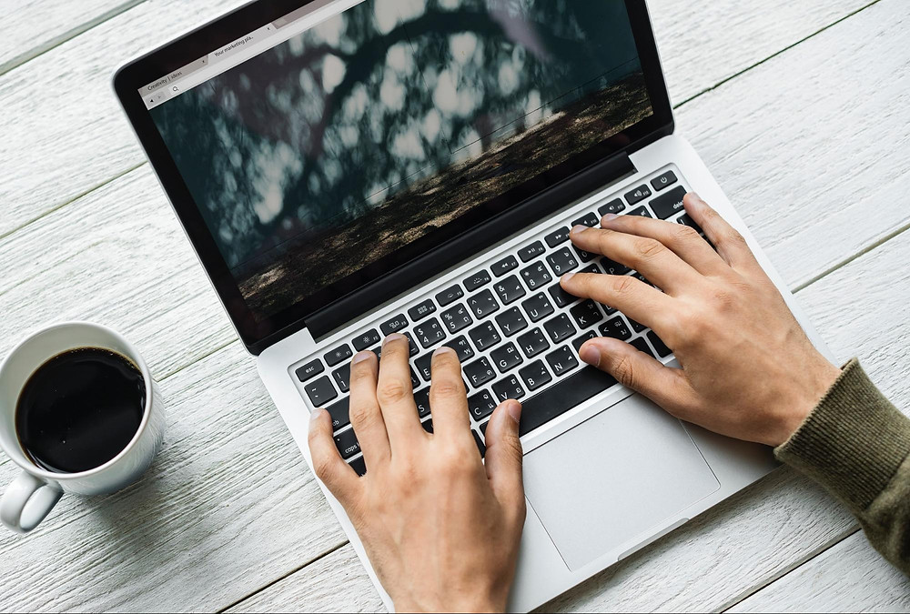 Man's hands typing on a MacBook Air keyboard with a cup of coffee.