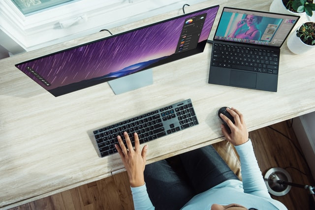 person using a computer with wireless keyboard and mouse