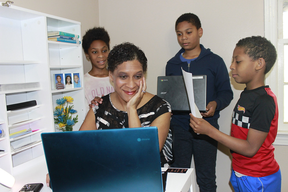 Mother at computer with three children around her asking for attention