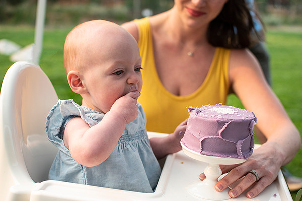 small baby eating cake with her mom