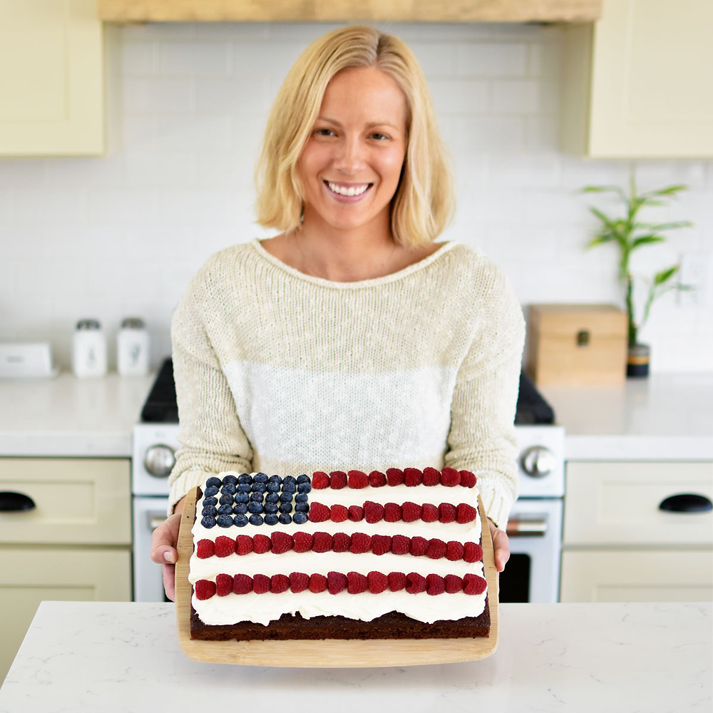 Easy Chocolate Berry Flag Cake with whipped cream frosting and fresh berries. This easy to make flag cake is perfect for Fourth of July celebration, Labor Day, or Memorial Day. Red, white, and blue flag cake design that's easy to make with fresh seasonal berries! #organiccake #flagcake #whippedcreamfrosting #homemadewhippedcream #freshberries #freshberrycake #chocolatecake #highaltitudebaking #highaltitudecake
