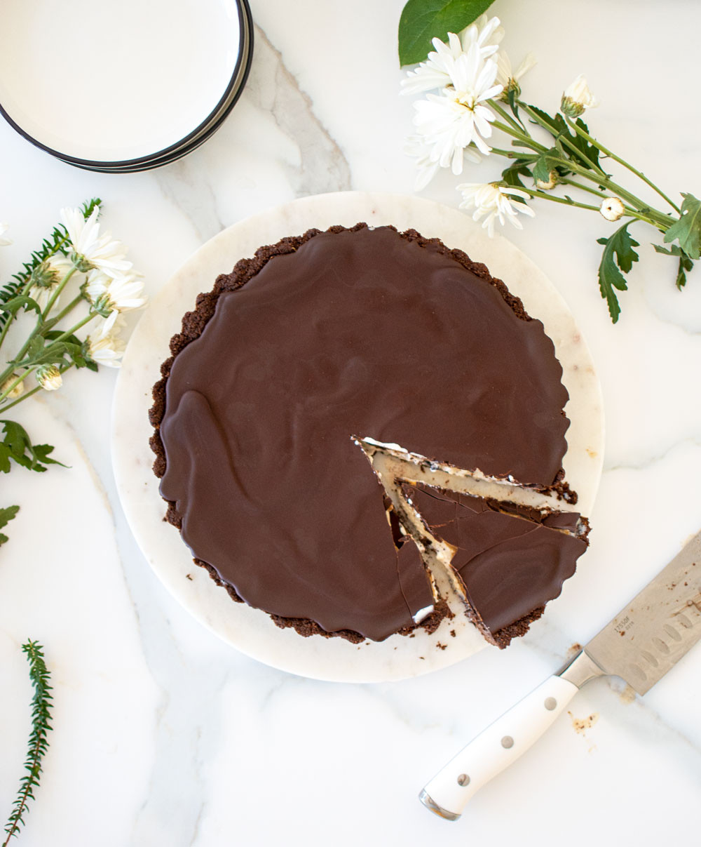 Delicious Chocolate Peanut Butter Ice Cream Tart, the best frozen dessert recipe for summer! This easy frozen tart recipe uses your favorite ice cream, peanut butter, and magic shell to create a homemade ice cream tart that you will love! Just need to make the chocolate graham cracker crust, and this tart is so easy to assemble and enjoy on a hot summer night. #tart #tartrecipe #organicicecream #icecreamtart #chocolatepeanutbutter